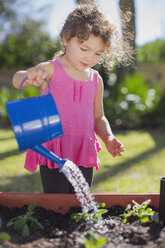Young girl in garden, holding watering can, watering plants in tub - ISF07122