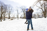 Romantic young man carrying girlfriend in snowy Central Park, New York, USA - ISF07223