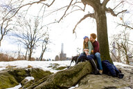 Romantic young couple sitting with dog in snowy Central Park, New York, USA - ISF07226