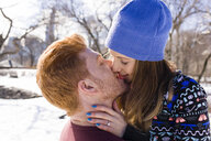 Romantic young couple kissing in snowy Central Park, New York, USA - ISF07229