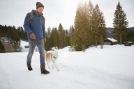 Young man walking husky in snow covered landscape, Elmau, Bavaria, Germany - CUF18951