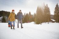 Parents pulling sons on toboggan in snow landscape, Elmau, Bavaria, Germany - CUF18954