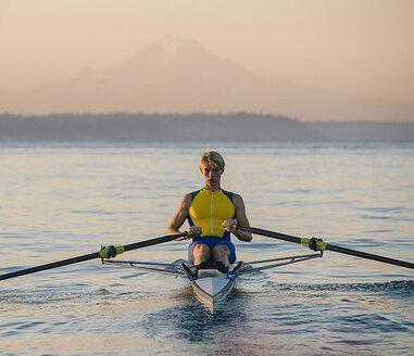 Teenage boy in sculling boat on water - ISF07235