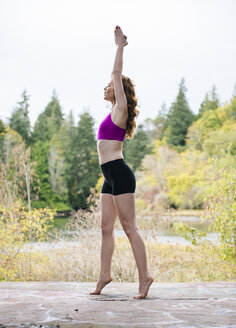 Side view of young woman practicing yoga on forest lakeside - ISF07265