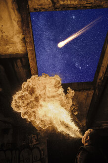 Low angle view of man fire breathing, meteor in starry night sky - ISF07325