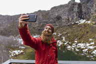 Iceland, smiling bearded man using smartphone, selfie - AFVF00550