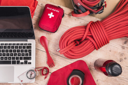Overhead view of climbing equipment packing with red first aid kit, climbing ropes and laptop - CUF19007