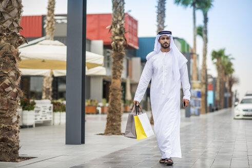 Man wearing traditional middle eastern clothing walking along street carrying shopping bags, Dubai, United Arab Emirates - CUF19121