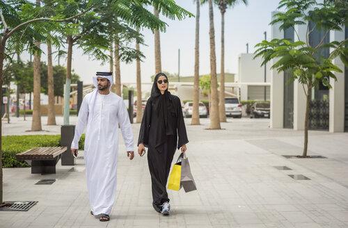 Middle eastern shopping couple  wearing traditional clothing walking along street, Dubai, United Arab Emirates - CUF19130