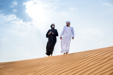 Couple wearing traditional middle eastern clothes walking on desert dune, Dubai, United Arab Emirates - CUF19139