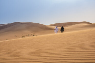 Distant view of couple wearing traditional middle eastern clothes walking on desert dune, Dubai, United Arab Emirates - CUF19145