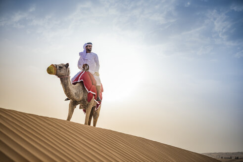 Man wearing traditional middle eastern clothes riding camel in desert, Dubai, United Arab Emirates - CUF19148