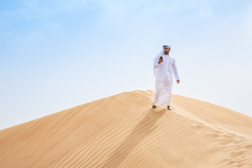 Middle eastern man wearing traditional clothes using smartphone on desert dune, Dubai, United Arab Emirates - CUF19214