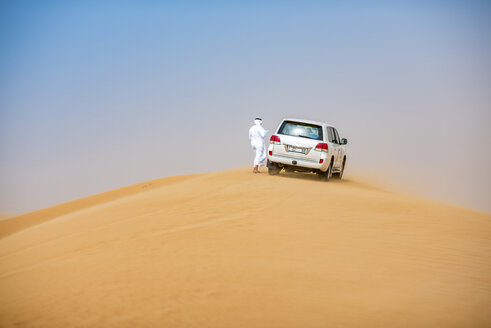 Middle eastern man wearing traditional clothes with off road vehicle parked on desert dune, Dubai, United Arab Emirates - CUF19217
