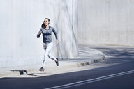 Female jogger with headphones on street - BSZF00433