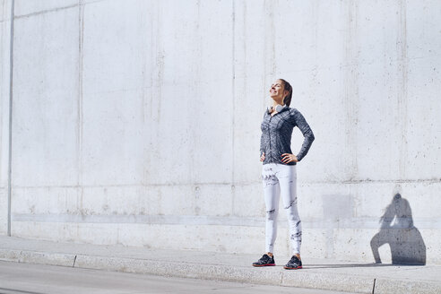Female jogger enjoying sunny day during urban workout - BSZF00436