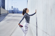 Female runner stretching legs during urban workout - BSZF00439