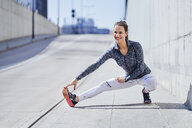 Female runner stretching legs during urban workout - BSZF00442
