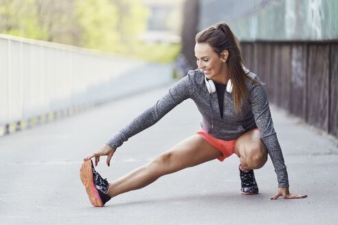 Female runner stretching legs during urban workout - BSZF00448