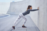 Female runner stretching legs during urban workout - BSZF00454