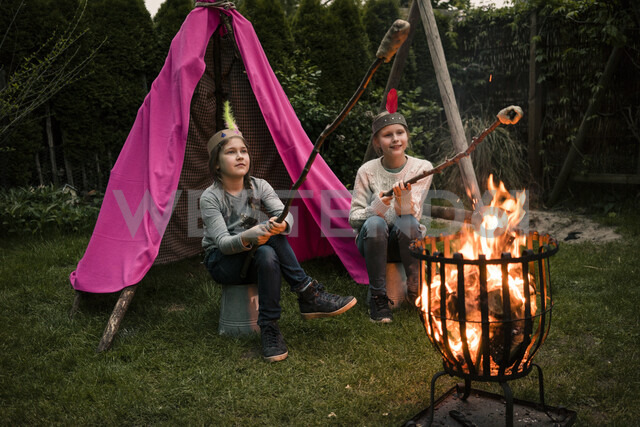 Two girls wearing feather headdress, with stock bread at camp fire - MOEF01213 - Robijn Page/Westend61