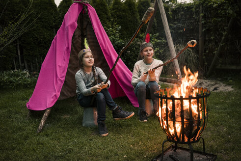Two girls wearing feather headdress, with stock bread at camp fire - MOEF01213