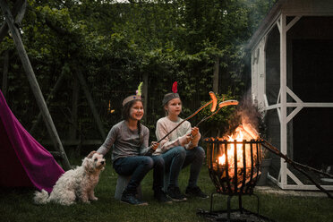 Two girls wearing feather headdress, grilling sausage over camp fire, dog sitting on meadow - MOEF01216