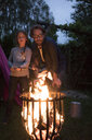 Father and daughter with twist bread looking into camp fire - MOEF01219