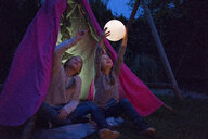 Two girls sitting in tipi, holding lamp as moon - MOEF01222