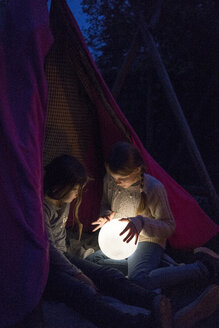 Two girls sitting in tipi, holding lamp as moon - MOEF01225