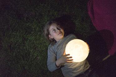Girl lying on meadow, holding moon - MOEF01228