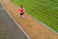 Aerial view of female jogger on woodchip trail - STSF01587