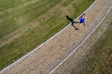 Aerial view of female jogger on woodchip trail - STSF01590