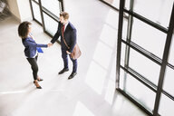 High angle view of businessman and woman shaking hands at  office entrance - CUF19472