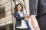 Low angle view of businesswoman shaking hands with businessman at office - CUF19478