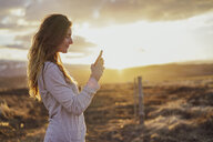 Iceland, young woman using smartphone at sunset - AFVF00555