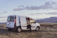 Iceland, young man leaning on van and playing guitar - AFVF00561