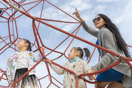 Mother with two daughters in climbing frame - AFVF00564