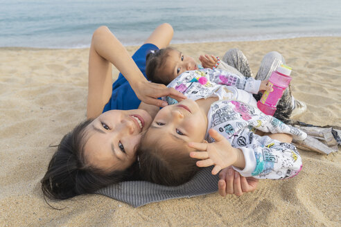 Happy mother with two daughters lying on the beach - AFVF00567