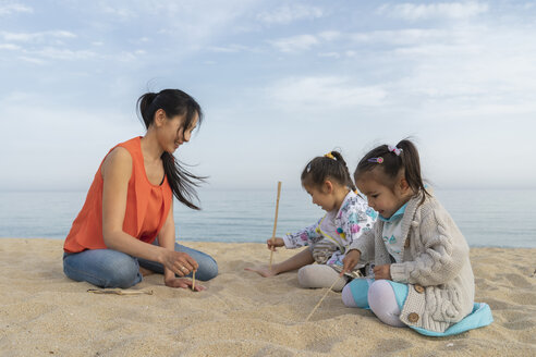 Mother with two daughters sitting on the beach - AFVF00570