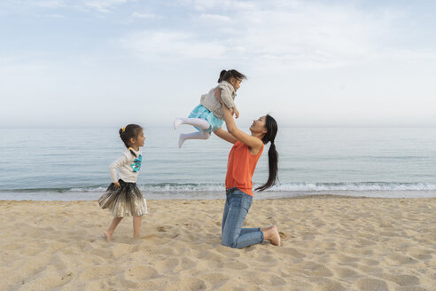 Happy mother with two daughters playing on the beach - AFVF00573