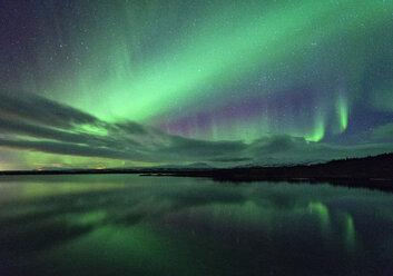 Aurora borealis over water, Thingvellir, Iceland - CUF19740