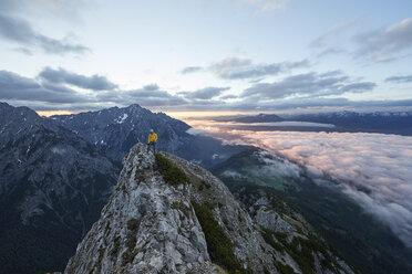 Austria, Tyrol, Gnadenwald, Hundskopf, male climber standing on rock in the morning light - CVF00631