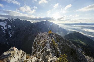 Austria, Tyrol, Gnadenwald, Hundskopf, male climber standing on rock in the morning light - CVF00634