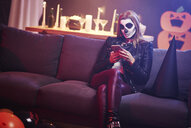 Bored woman using mobile phone at Halloween party - ABIF00465