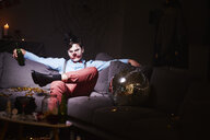 Man in Halloween costume sitting on couch after party, drinking beer - ABIF00516