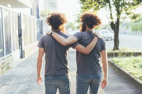 Rear view of identical male adult twins strolling on sidewalk - CUF19802