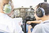 Rear view of pilot and co-pilot sitting in aircraft, talking through flight plan - CUF19820