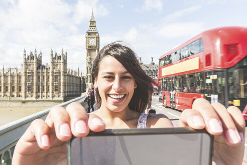 Young woman taking selfie with smartphone, Houses of parliament and Big Ben in background - CUF19835