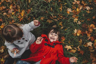 Overhead portrait of girl and toddler sister lying on grass and autumn leaves - ISF07435